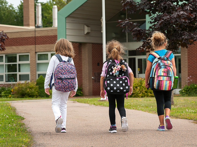 Three children walking into school