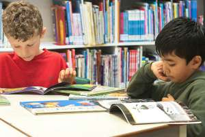Two boys reading in a school library