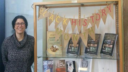 Librarian Beth Clinton stands next to a display for Black History Month