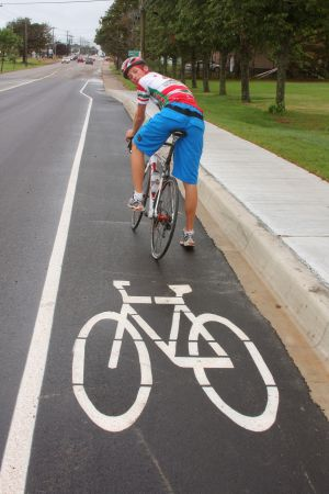 Young cyclist who is riding in a bike lane is looking over his shoulder to merge into traffic as the bike lane ends