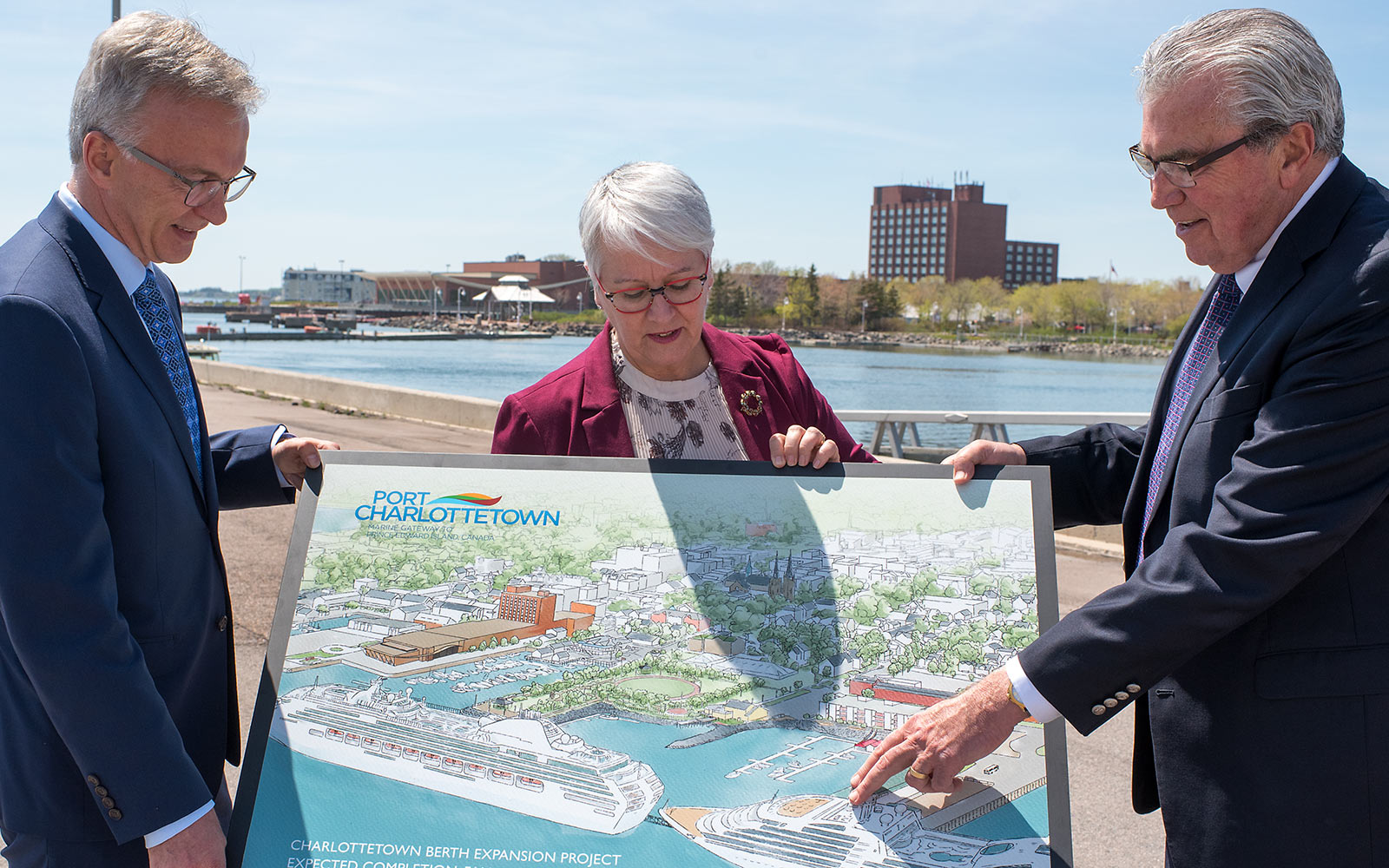 Sean Casey, Paula Biggar and Stan MacPherson look over the artist rendition of the newly expanded Port of Charlottetown