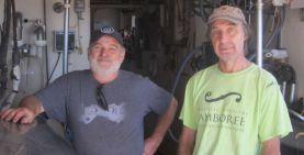 Brothers Johnny and Gary Gallant stand in milking parlour of their dairy farm