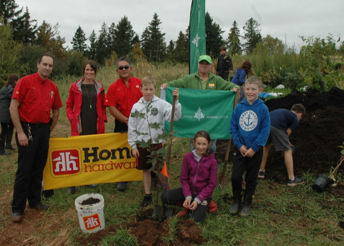 Students and adults stand with shovels and dirt, ready for tree planting.