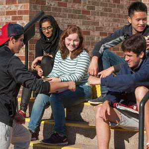 Group of high school students sitting outside on steps to school