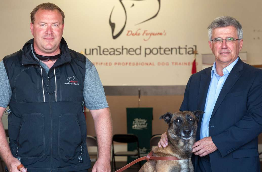 Pictured from left to right is Duke Ferguson, CEO of Unleashed Potential K9 Academy and Minister Richard Brown of the Department of Workforce and Advanced Learning along with a german shepherd. The location is Unleashed Potential K9 Academy in Stratford.