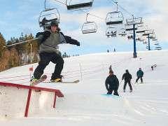 Young guy hits a snowboard jump at Brookvale Ski Park