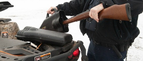 A Conservation Officer is shown placing a firearm into a case for transport.