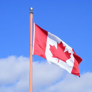 Canadian flag flying against blue sky