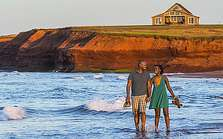 Couple walking on beach near Thunder Cove, PEI