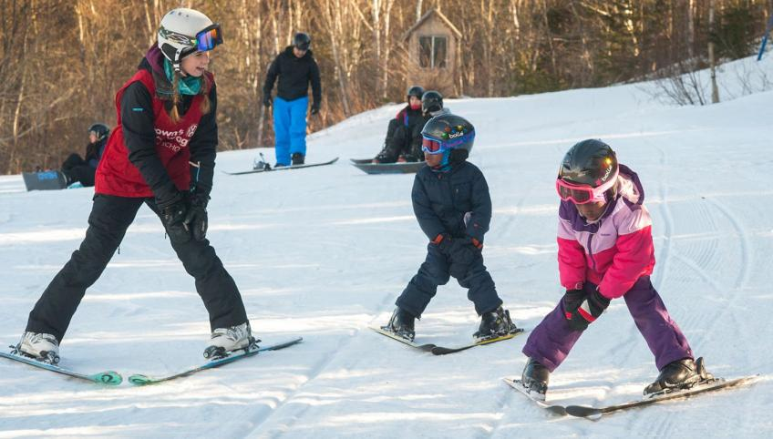 Ski instructor teaches two young children how to stop during skiing lessons