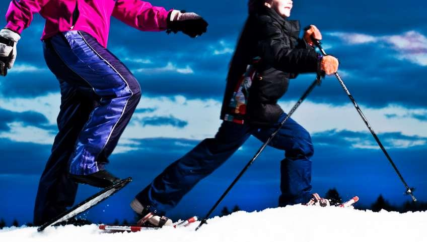 Woman and young boy snowshoeing under bright blue sky