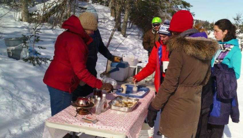Group of people watch a demonstration of making maple candy at winter woodlot tour