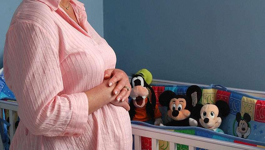 Pregnant woman stands beside baby crib