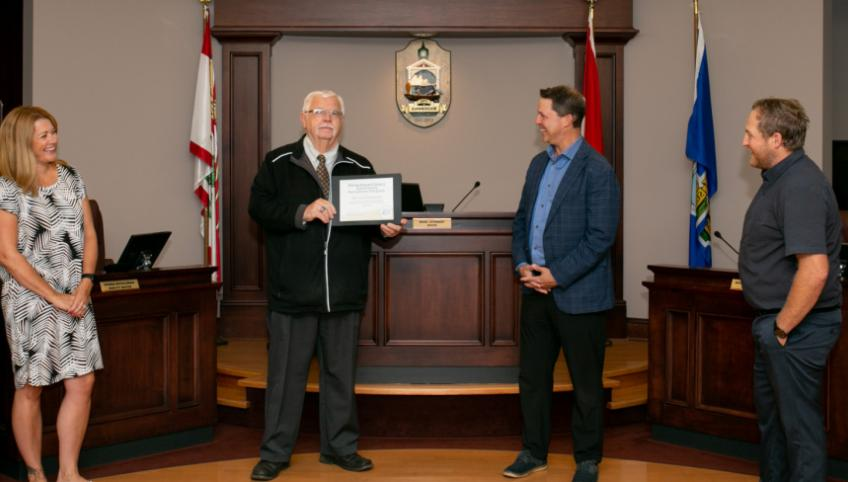 Four officials stand in the Summerside City Hall, with the Mayor holding a certificate.