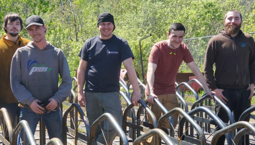 Holland College students standing behind a set of bike racks they built.
