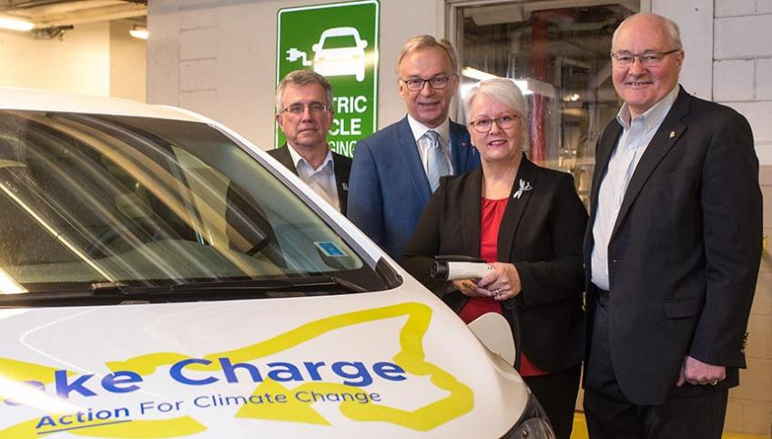 Richard Brown, Sean Casey, Paula Biggar and Wayne Easter stand beside an electric car in front of a charging station