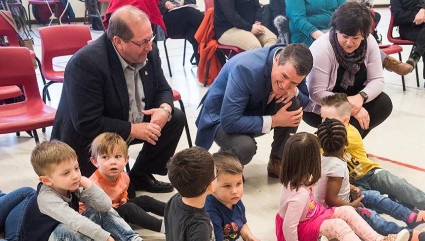 Three adults crouch on the floor where day care children are sitting