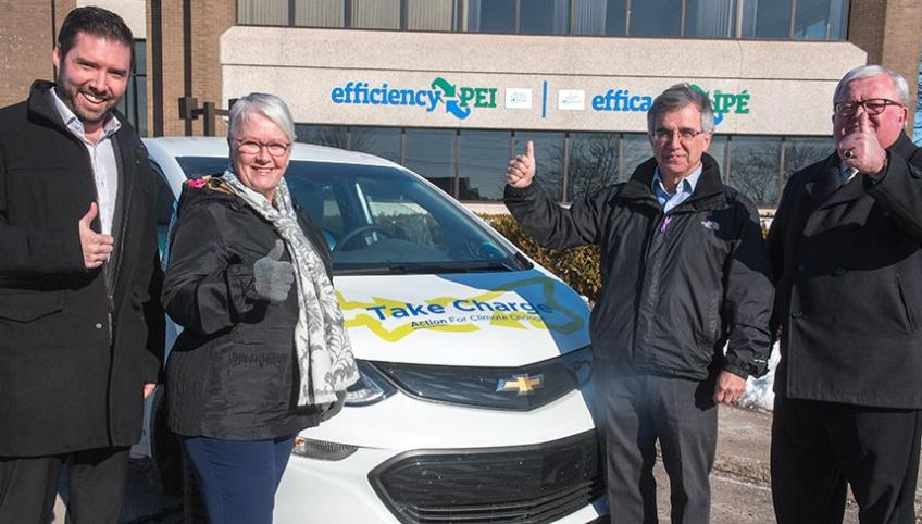 Four people stand beside an electric car in front of the efficiencyPEI building