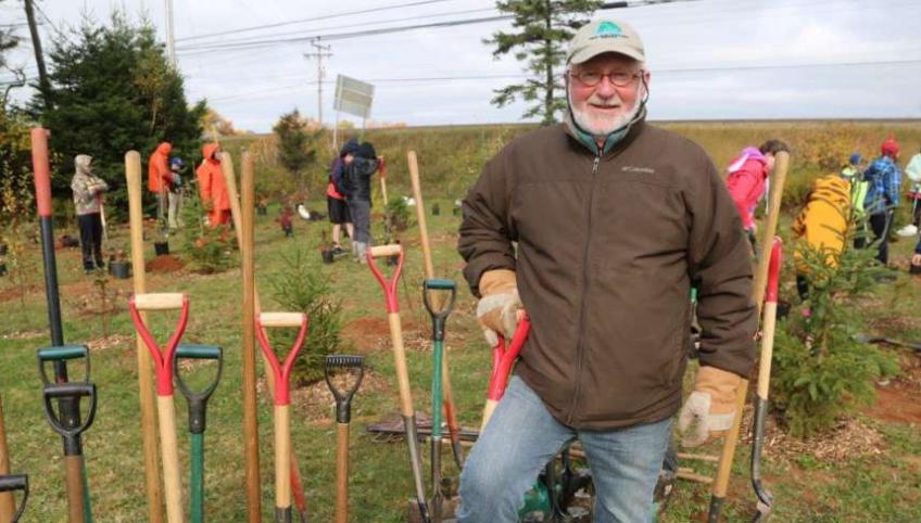 Bill Hogg stands beside a row of shovels with students planting trees in the background