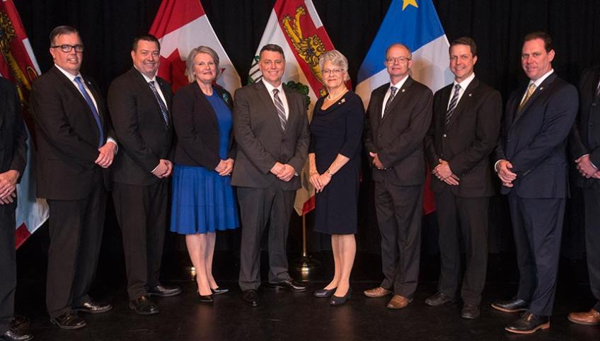 Members of the new government cabinet, standing in a row with the Lieutenant Governor