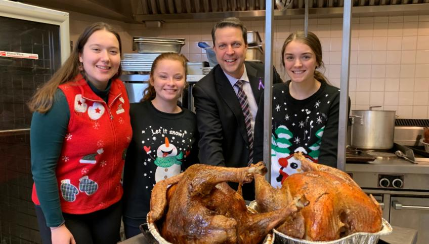 Four people standing in a kitchen behind two cooked turkeys