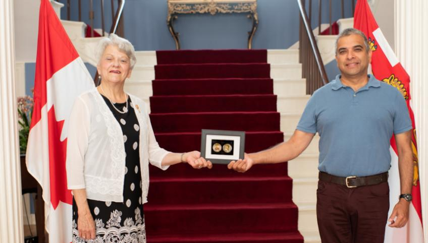 Honourable Antoinette Perry and Dr. Trevor Jain stand holding a COVID Warrior Coin