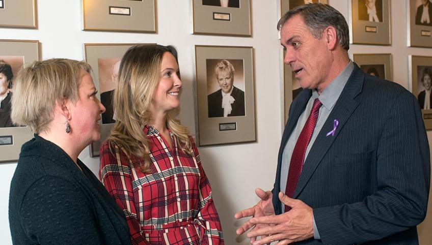 Tara Roche, RN, and Shauna Wright, NP, stand talking with Health Minister Robert Mitchell
