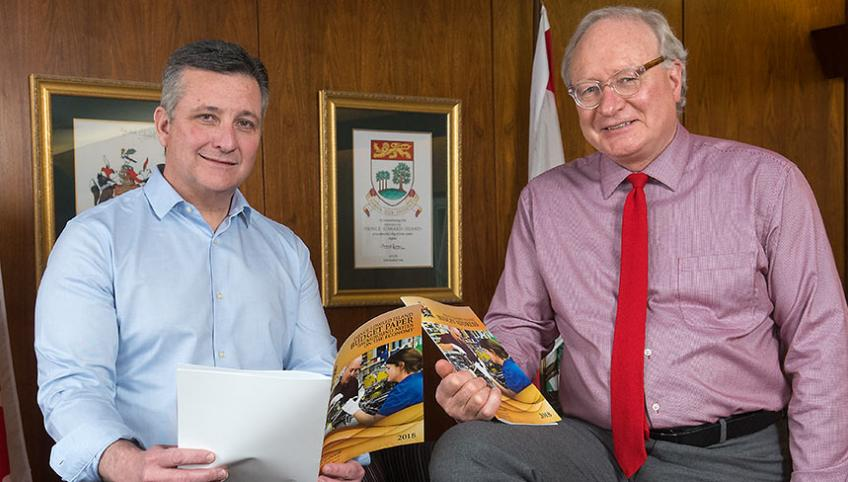 Photo shows Minister Heath MacDonald and Premier Wade MacLauchlan holding copies of the 2018-19 operating budget.