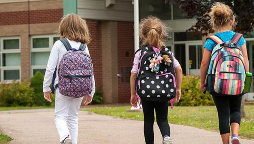 three children walking toward a school