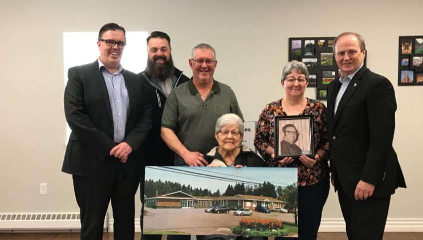 Minister Myers and four Islanders stand behind a woman sitting holding a large photo of the proposed Tignish co-op expansion