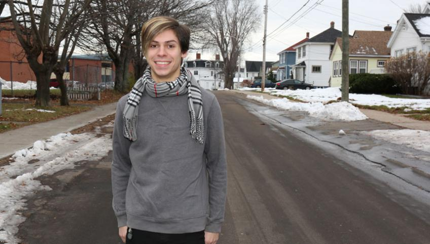 Tyler Murnaghan stands alone on a snowy city street smiling at the camera.