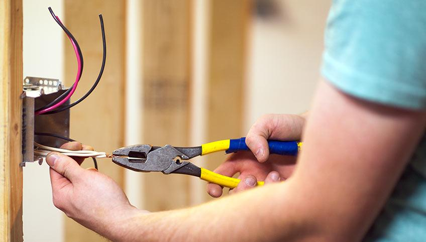 Image of male electrical contractor wiring an outlet