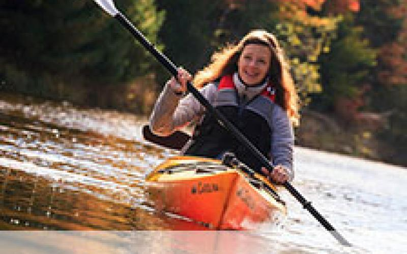 """Image of female kayaking down river in autumn with title """"About PEI"""""""