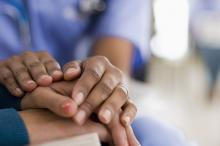 A health professional has their two hands on top of a woman's hands showing comfort.
