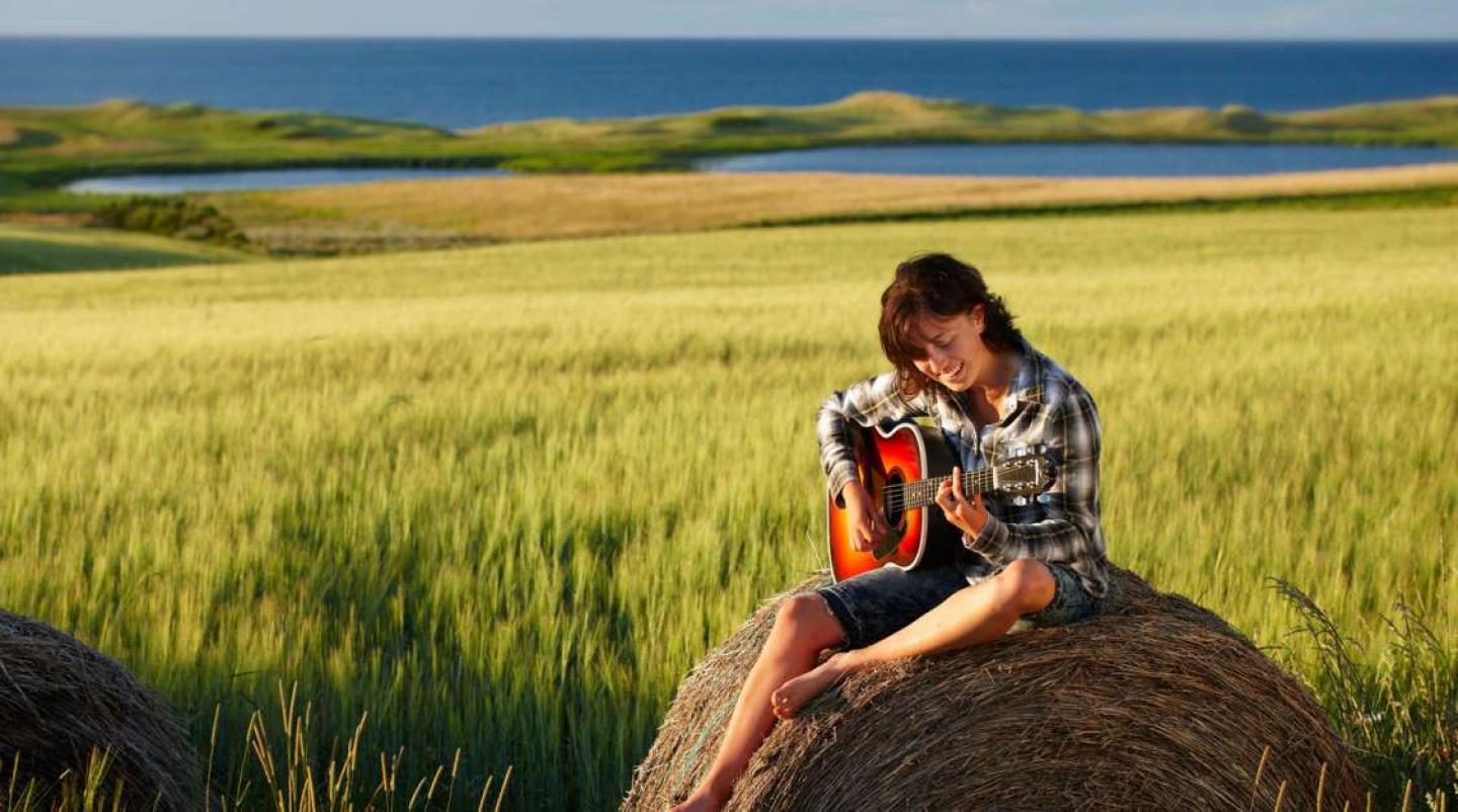 Woman sitting on top of hay bale playing guitar with ocean in background