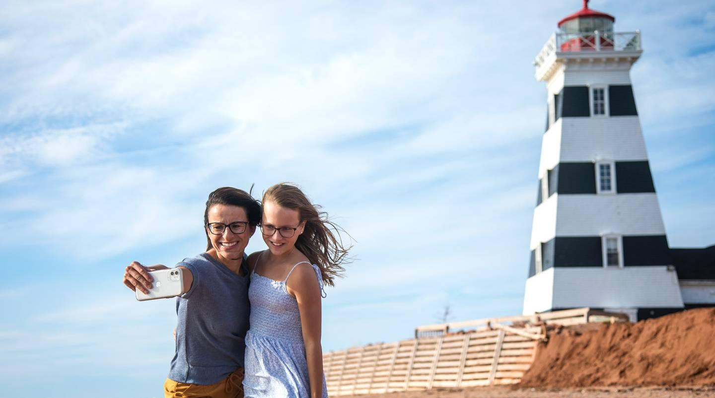 two people taking a photo in front of a lighthouse