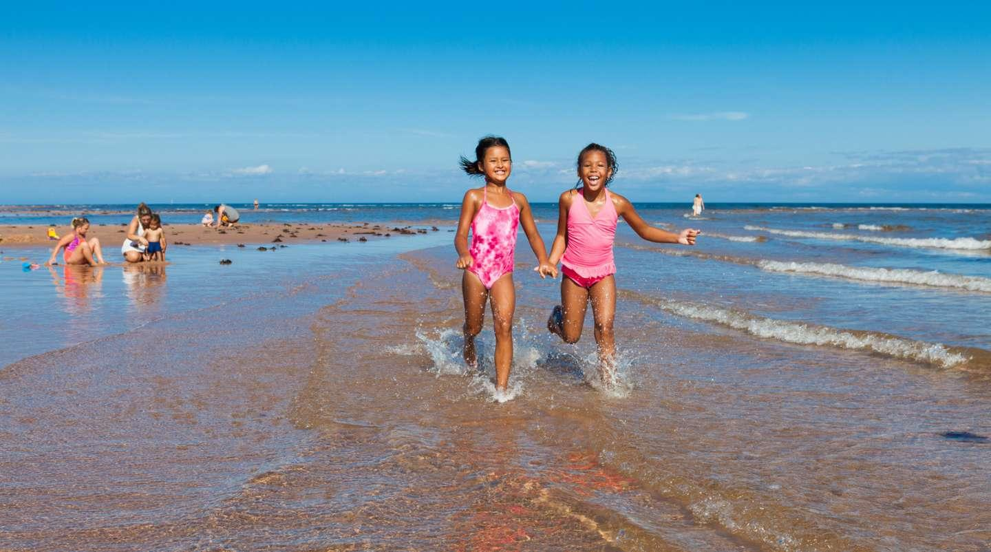 Children playing at Singing sands at Basin Head provincial park