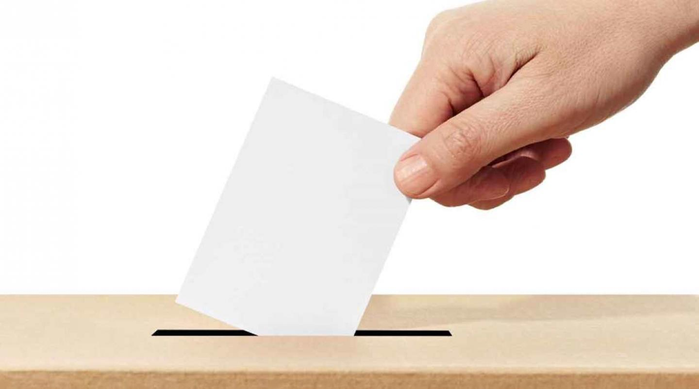 Person dropping ballot into election box