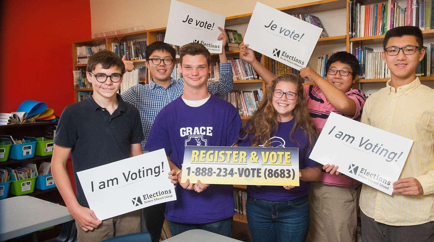 "Group of young voters holding sign saying ""Je Vote!"" and ""Iam Voting!"""
