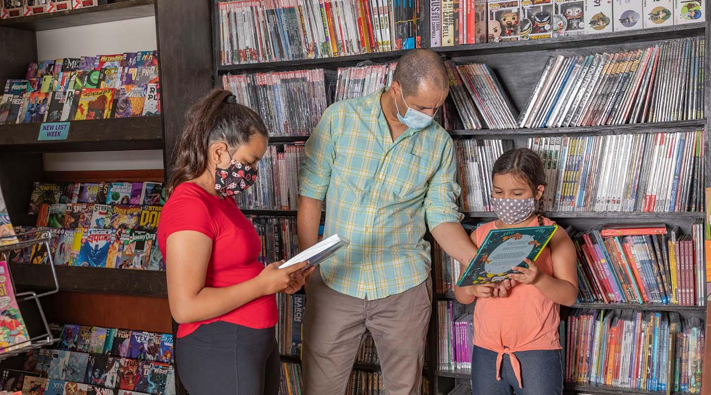 family in a bookstore wearing masks