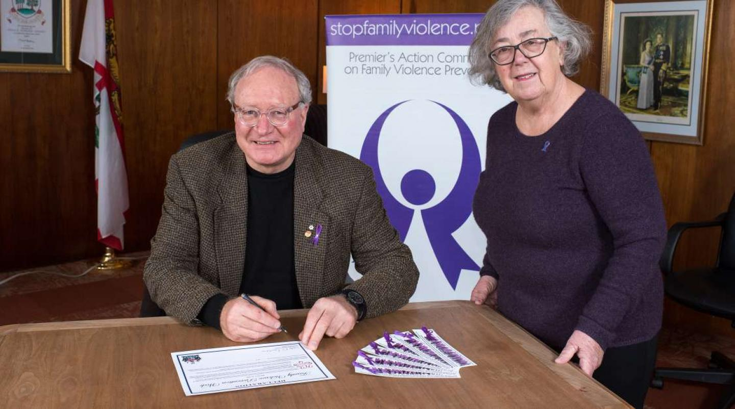 PEI Premier Wade MacLauchlan signs a proclaimation with Anne Sherman, chair of the Premier's Action Committee on Family Violence Prevention to mark events of 2018