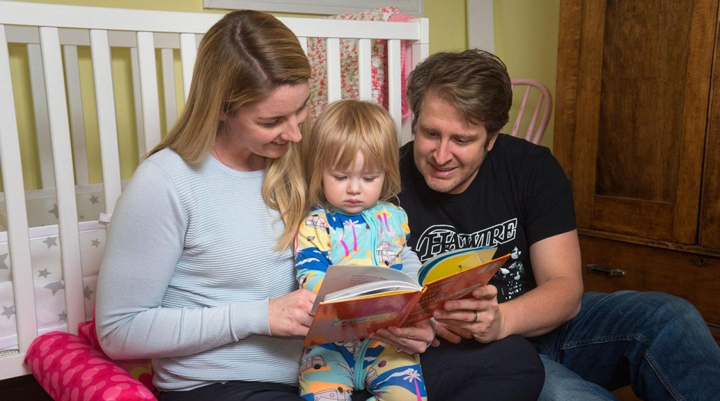 Parents with small child reading a bedtime story
