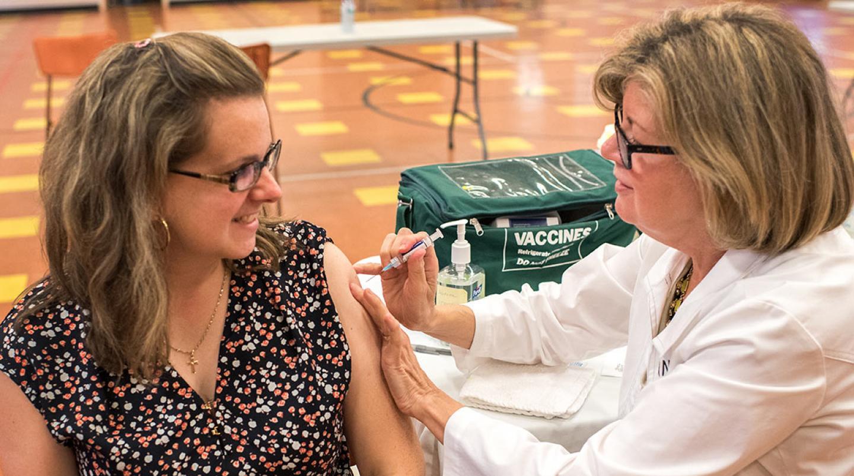Public health nurse gives a lady her flu shot