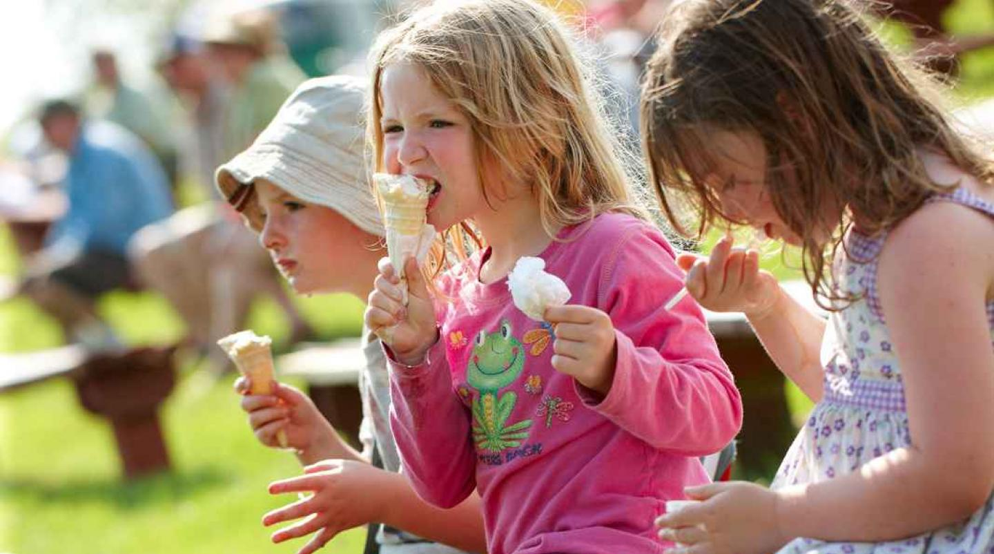 Children eating ice cream outdoors at a summer event