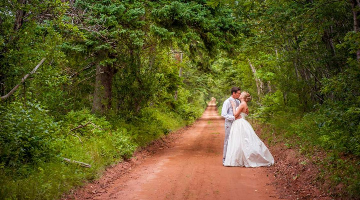 Newly weds kissing on heritage road near Rustico, PEI