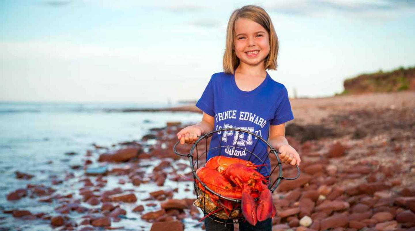 YOung girl holds basket of lobster on PEI beach