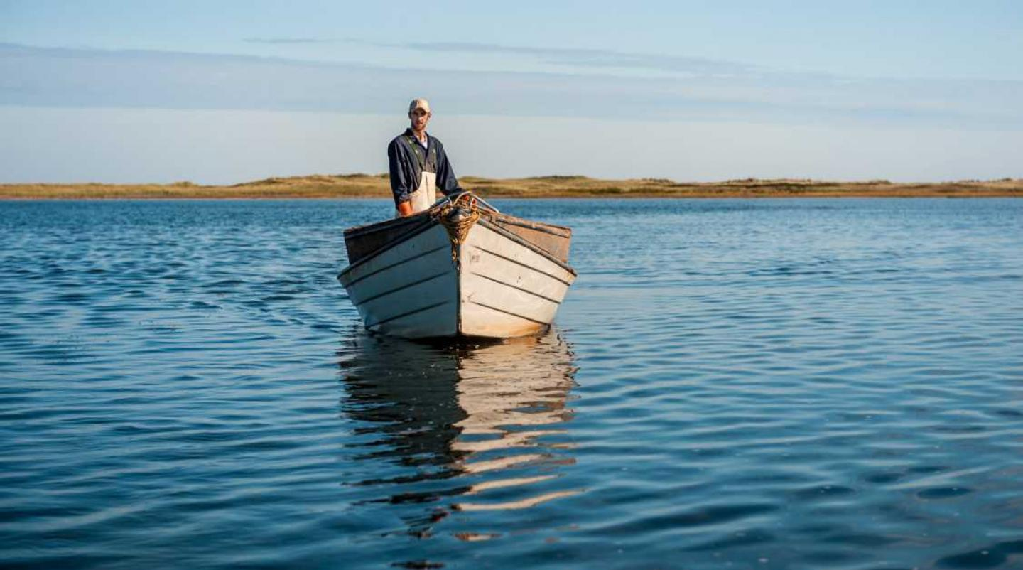 PEI oyster farmers stands upright in dory
