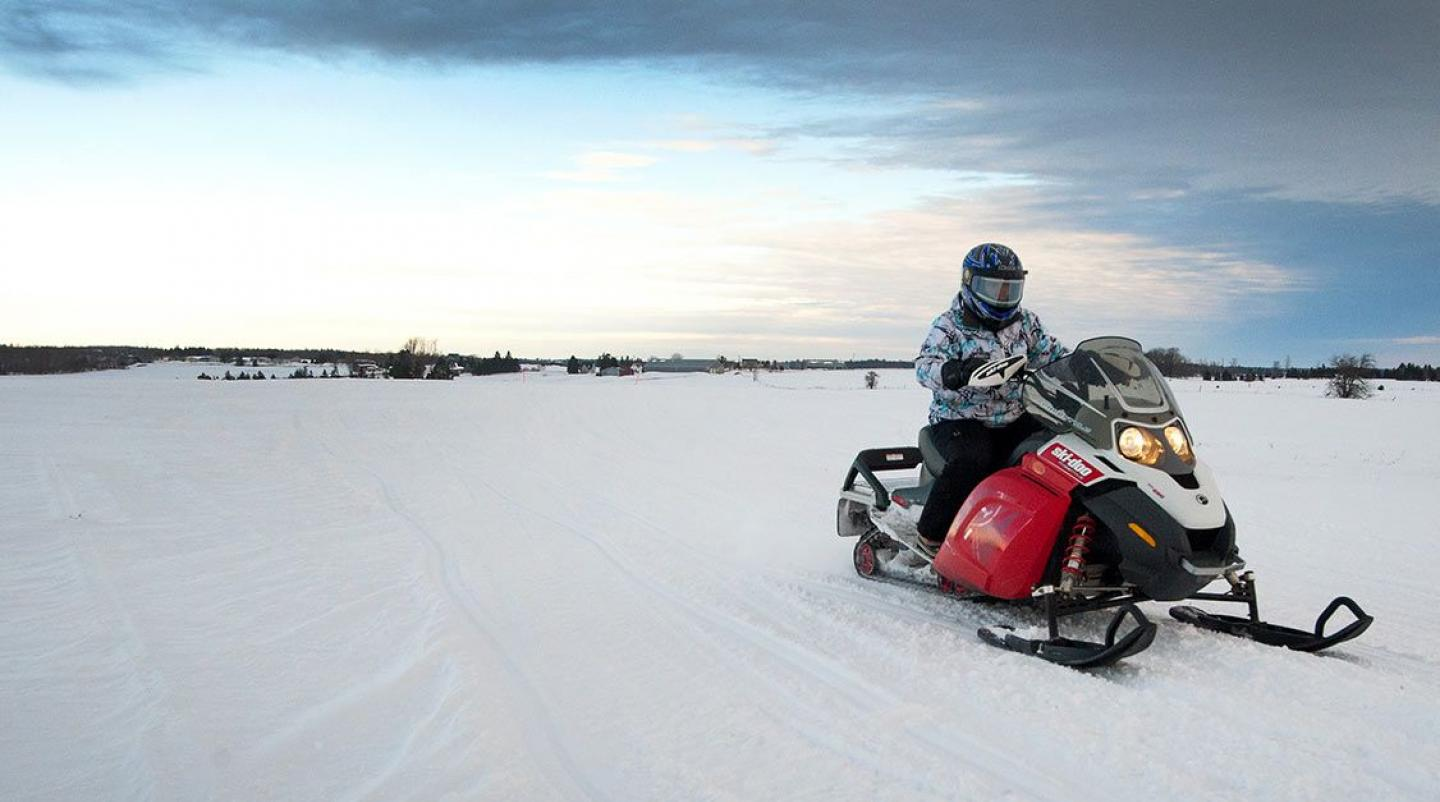 Snowmobile rider in foreground with PEI farm in background at dust