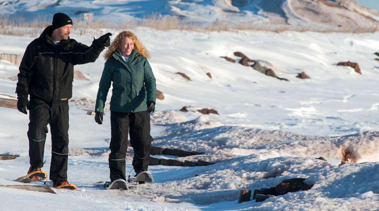 Male and female snowshoeing in PEI National Park, Rustico