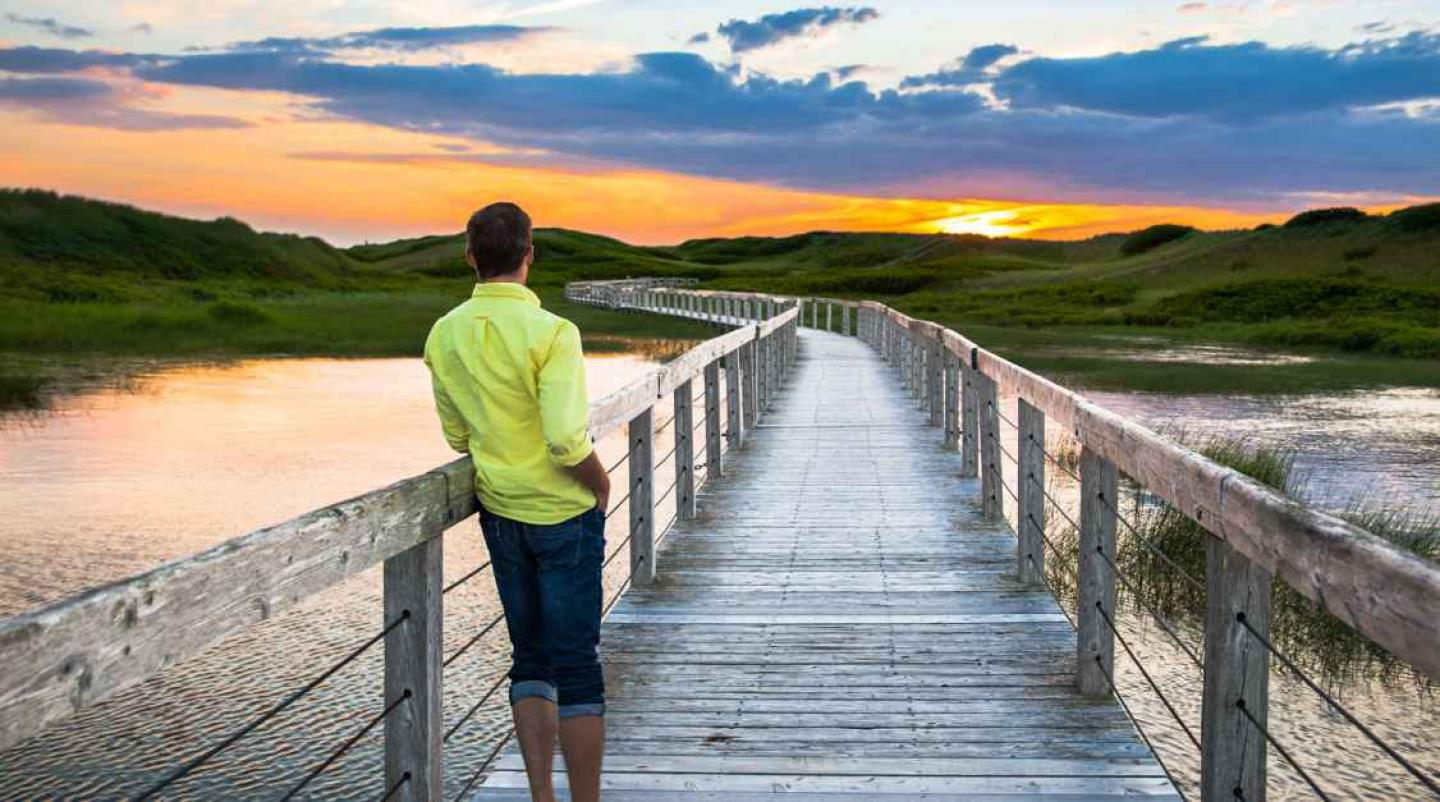 Young man stands alone on boardwalk at Greenrich National Park watching a sunset